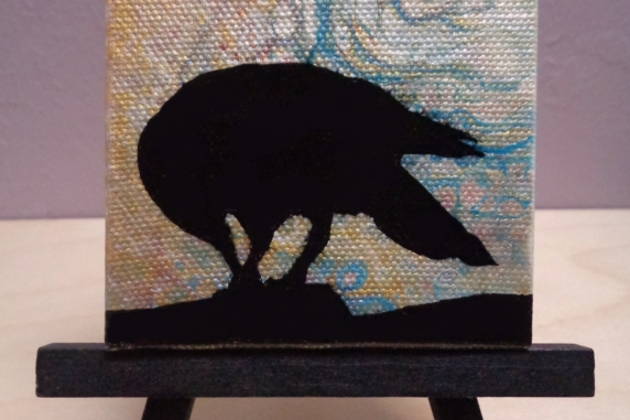 Crow painting on easel